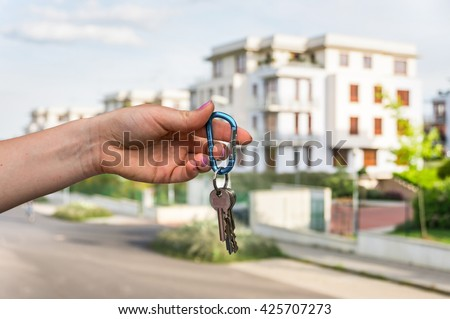Real estate agent giving house keys to a new property owner on blurred background - stock photo