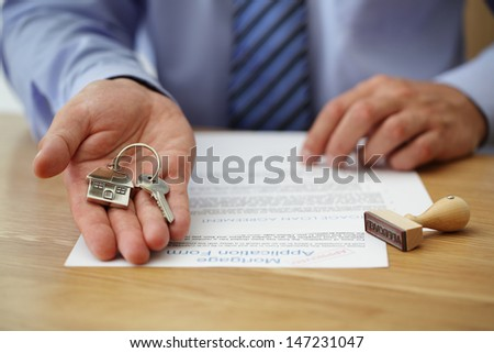 Real estate agent handing over house keys with approved mortgage application form - stock photo