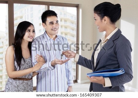 Real estate agent handing over keys of new house to young couple - stock photo