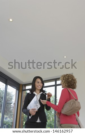 Real estate agent handing woman keys in new property - stock photo