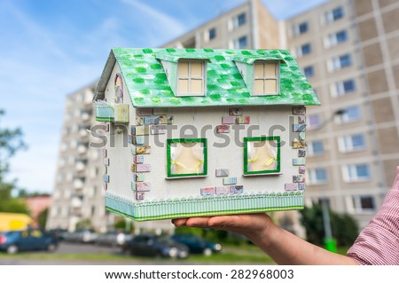 Real estate agent holding model house from paper on blurred background - stock photo