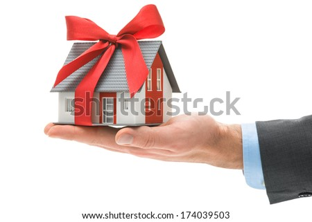 Real estate agent holds architectural model with red bow - stock photo