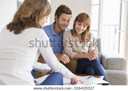 Real estate agent presenting a contract for house investment to futur owners couple - stock photo