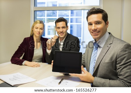 Real-estate agent presenting a new project on tablet pc, young couple background  - stock photo