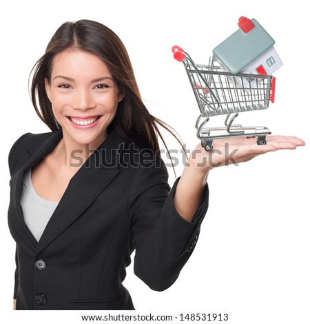 Real estate agent selling home holding mini house in shopping cart. Female realtor in business suit showing model house smiling happy isolated on white background. Multiracial Asian woman agent. - stock photo