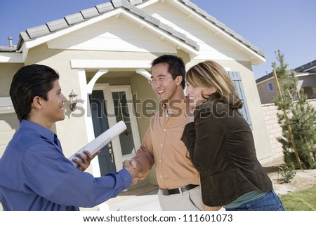 Real estate agent shaking hand with couple buying new house - stock photo