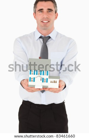 Real estate agent showing a miniature house against a white background - stock photo