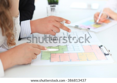 Real-estate agent showing house plans - stock photo