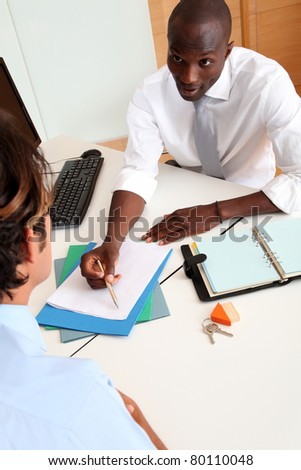 Real-estate agent with couple signing contract - stock photo