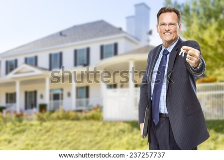 Real Estate Agent with House Keys in Front of Beautiful Home. - stock photo