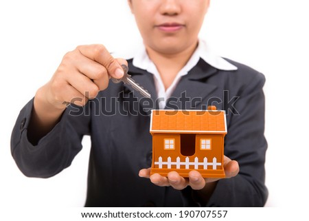 Real estate agent with house model and keys - stock photo