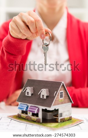 Real estate agreement. Client buying new house in broker office. Close-up of female realtor's hand with key ring. Shallow depth of field. - stock photo