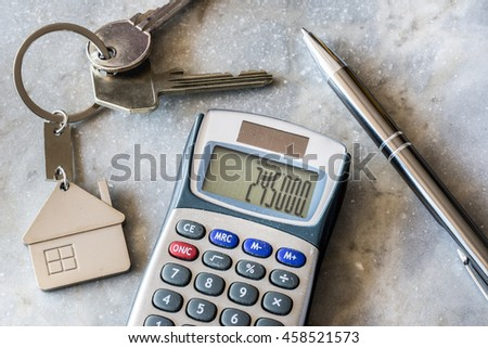 Real estate and mortgage concept. Calculator, keys and pencil on marble background. - stock photo