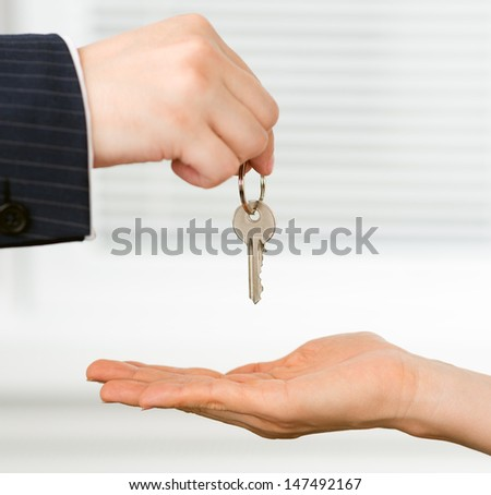 Real estate broker handing a key of a new flat to a woman. House purchase concept.  - stock photo