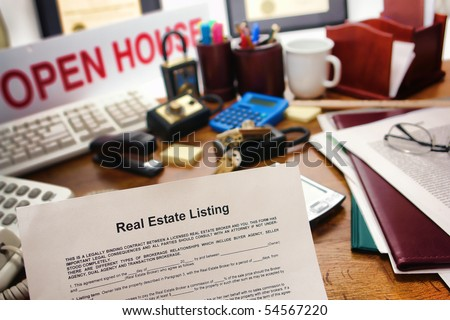 Real estate broker listing contract over busy Realtor desk in realty agent resale office (fictitious document with authentic legal language)  - stock photo