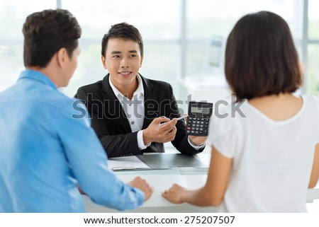 Real estate broker showing price of the house to his clients - stock photo