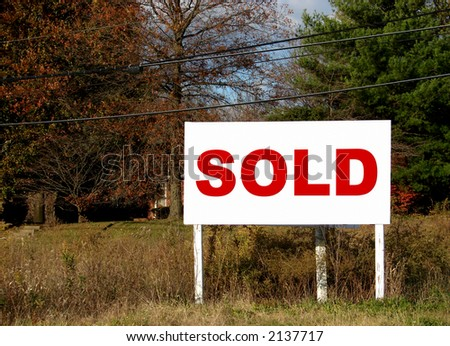 Real estate commercial size sold sign in a field advertising an empty lot for sale - stock photo