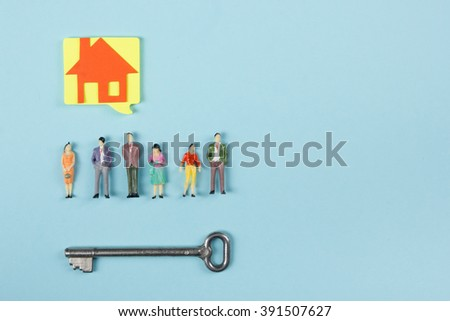 Real Estate concept. Blank speech bubbles and people toy figures Construction, building. Paper model house with key on blue background. Top view. Copy space for text. - stock photo