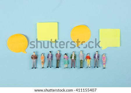 Real Estate concept. Blank speech bubbles and people toy figures Construction, building. Paper model house with key on blue background. Top view. Copy space for text - stock photo
