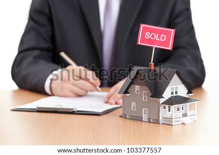 Real estate concept - business man signs contract behind house architectural model - stock photo