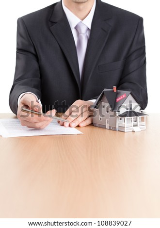 Real estate concept - business-man signs contract behind household architectural model - stock photo