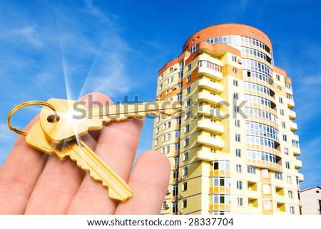 real estate concept. gold keys in fingers with building - stock photo