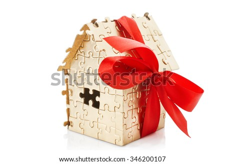 Real estate concept - house of gold color puzzles with red bow