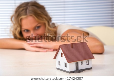 real estate concept with happy businesswoman and mini house - stock photo