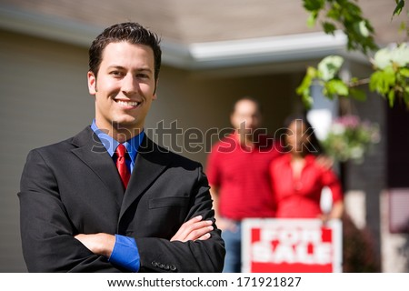 Real Estate: Confident Agent With Home Sellers Behind - stock photo
