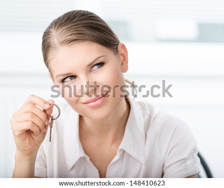 Real estate female customer holding a key of a new apartment in realtor's office. Smiling  blond Caucasian female buying flat.    - stock photo