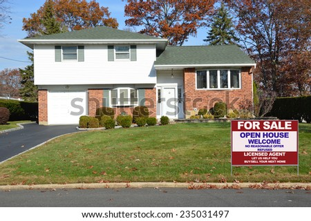 Real Estate For sale open house welcome sign front yard of Suburban Brick High Ranch home autumn day residential neighborhood clear blue sky USA - stock photo