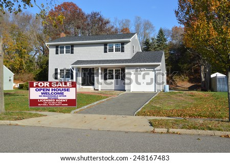 Real estate for sale open house welcome sign Suburban Gray High Ranch home autumn day residential neighborhood clear blue sky day USA - stock photo