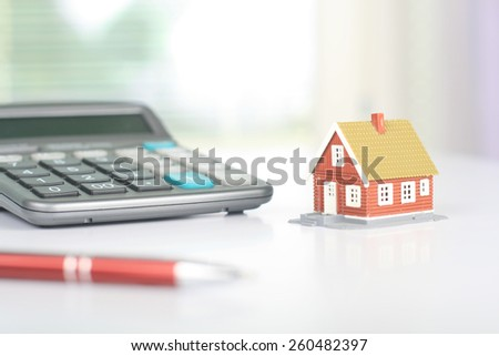 Real estate investment. House and calculator on table. - stock photo