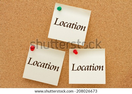 Real Estate Location, Location, Location, Three yellow sticky notes on a cork board with the words Location - stock photo