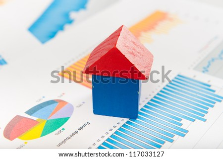 Real estate market concept with graphs and house from toy blocks - stock photo