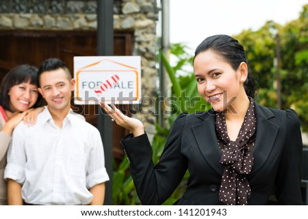 Real estate market - young Indonesian couple looking for real estate apartment or house to rent or buy - stock photo
