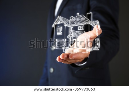 Real estate offer. Businessman holds an artificial model of the house - stock photo
