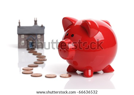 Real estate or home savings - red piggy bank, coins and a house - stock photo