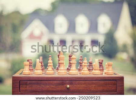Real estate sale, home savings, loans market concept. Housing industry mortgage plan and residential tax saving strategy. Chess game figures isolated outside home background. - stock photo