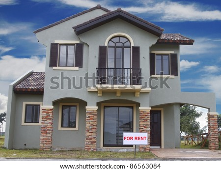 Real estate sign in front of a house for rent with blue clouds. - stock photo
