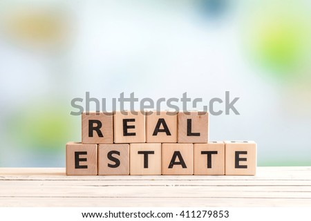 Real estate sign made of blocks on a wooden table - stock photo