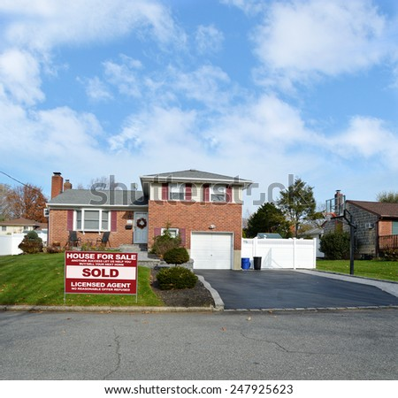 Real estate sold (another success let us help you buy sell your next home) sign Beautiful Suburban Brick Snout style home landscaped yard residential neighborhood USA blue sky clouds - stock photo