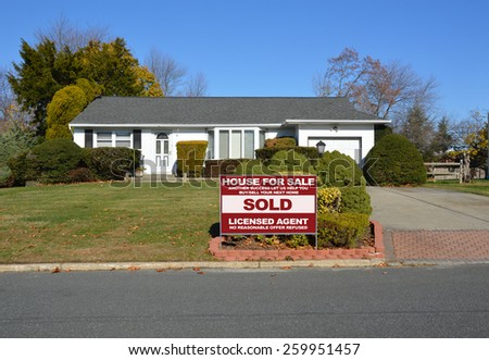 Real estate sold (another success let us help you buy sell your next home) sign Suburban Ranch style home clear blue sky residential neighborhood USA - stock photo
