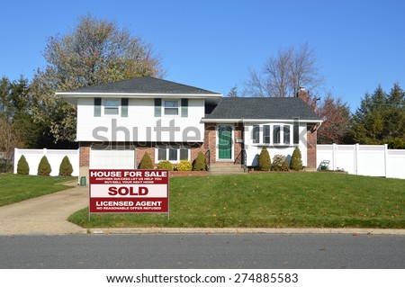 Real estate sold (another success let us help you buy sell your next home) sign Suburban Ranch home sunny clear blue sky residential neighborhood USA - stock photo