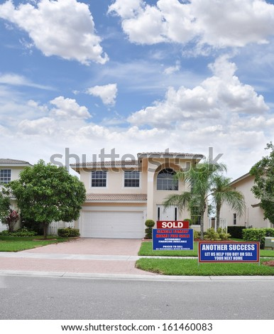 Real Estate Sold Sign Another Success Let us Help you Buy Sell your next home Sunny Blue Sky Suburban Home with landscaped front yard lawn Residential Neighborhood USA - stock photo