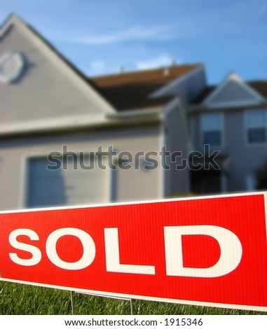 Real estate sold sign rider on Realtor advertising sign in front of a house for sale - stock photo
