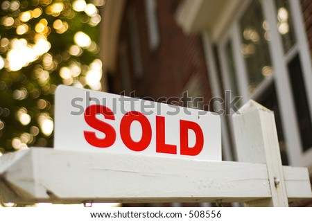 """Real Estate """"sold"""" sign with red brick building and trees blurry in the background - stock photo"""