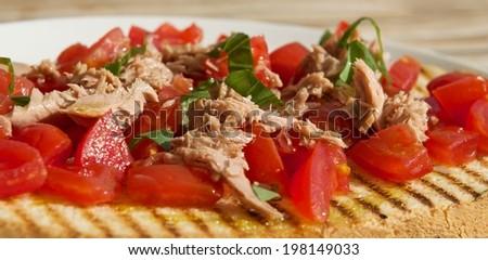 Real italian brucheta,sicilian food, fresh snack in Sicily, italian kitchen,sicilian kitchen, Italian Appetizer Bruschetta with  tomatoes, tuna, garlic and herbs - stock photo