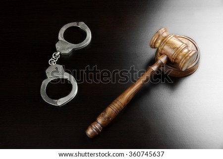 Real Judges Gavel, Sound Block  And Handcuffs On The Empty Black Table In The Back Light. Overhead View. - stock photo