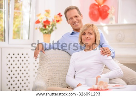 Real love. Nice agreeable smiling couple sitting in the armchair and  bonding to each other while expressing gladness - stock photo